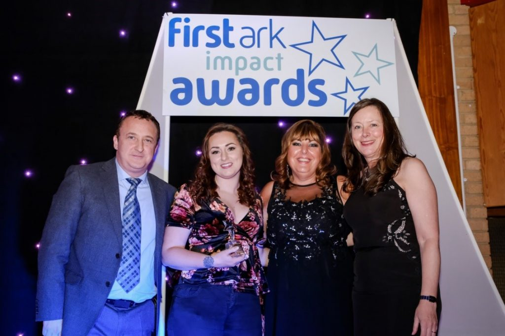 Keri Romano, Project Coordinator holding the trophy, next to Joyce Greaves, CEO who are both flanked by Neil Fitzmaurice, compere for the event and Jane Trevithick from Anthony Collins Solicitors who sponsored the award.